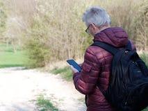 Mann in seine Siebziger, die seinen Smartphone betrachten lizenzfreie stockfotografie
