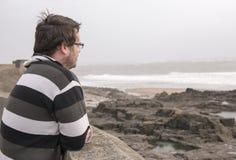 Mann in seine späten Zwanziger Jahre, die heraus in Richtung des Meeres an einem windigen Tag blicken Stockbild