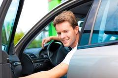 Mann in seinem Auto an der Tankstelle Lizenzfreies Stockfoto
