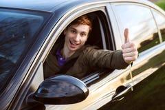 Mann in seinem Neuwagenshowdaumen oben Lizenzfreie Stockbilder