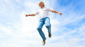 Mann in seinem 50s, das hoch springt Stockfotos