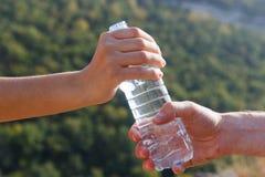 Mann sendet Frauenwasserflasche auf Camping-Ausflug im Wald Lizenzfreie Stockbilder