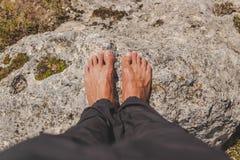 Mann setzte barfuß auf einen Felsen lizenzfreie stockfotos