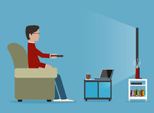 Mann sieht auf Sofa, vor Zeitschriftentabelle fern Stockfoto