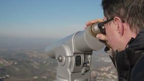 Mann sieht Natur und Marksteine durch Teleskop an stock video footage