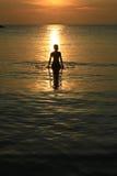 Mann sihouette im Meer und im Sonnenaufgang Stockbilder