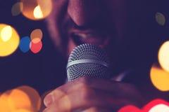 Mann singt Karaoke in einer Stange Stockbild