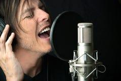 Mann singt in Kondensator-Mikrofon Stockfotografie