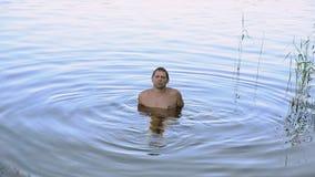 Mann sitzen auf Unterseite von See, die Erhöhungsfüße Überwasser im See am sonnigen Tag des Sommers nave erholung stock footage