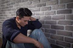 Mann sitzen und fühlen sich deprimiert Lizenzfreie Stockfotografie