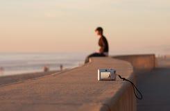 Mann-sitzender allein Sonnenuntergang-Strand und Kamera Lizenzfreie Stockfotos