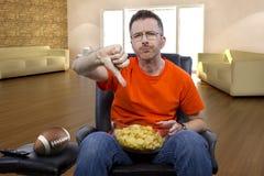 Mann-sitzender und aufpassender Fußball zu Hause Stockfotos