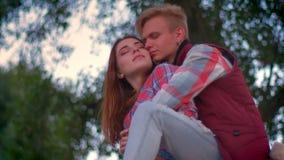 Mann sitzt auf dem Zaun, während seine Freundin nahe ihm steht und ist gehalten und nach vorn an schaut, grüne Bäume stock video