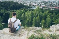 Mann sitzt auf der Spitze und dem Denken Stockbilder