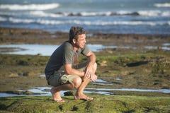 Mann sitzt auf seinen honches auf Felsen durch Ozean Lizenzfreies Stockbild