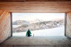 Mann sitzt in der hölzernen Hangarespritansicht auf schneebedecktem Gebirgstal Lizenzfreies Stockbild