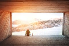 Mann sitzt in der hölzernen Hangarespritansicht auf schneebedecktem Gebirgstal Stockfotos