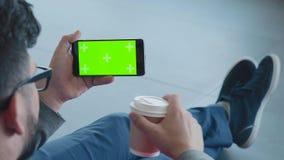 Mann sitzt in der Lobby, trinkt Kaffee, betrachtet den Schirm des Telefons stock video footage