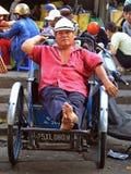 Mann sitzt in einem Warenkorb auf Straßenmarkt in der Farbe, Vietnam Stockbilder
