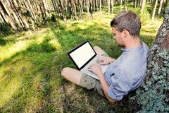 Mann sitzt gegen einen Baum im Wald und arbeitet mit seinem La Stockfotos