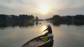 Mann sitzt im Boot, das Fischernetze gegen Sonnenaufgang hält stock footage