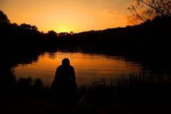 Mann sitzt mit Fischereigerät und -fischen auf Querneigung Stockfotografie