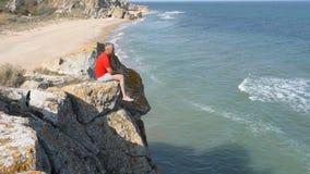 Mann sitzt am Rand einer Klippe Wellen waschen das sandige Ufer Ridge ist auf den Felsen defekt stock video