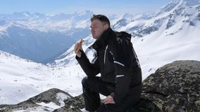 Mann-Skifahrer, der ein Sandwich-Mittagessen in den Bergen Ski Resort isst stockfotografie