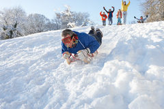 Mann Sledging unten Hügel mit dem Familien-Überwachen Stockbilder