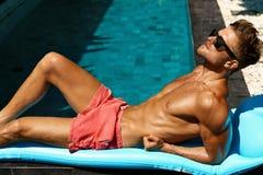 Mann-Sommer-Mode Männliches vorbildliches Tanning By Pool Haut Tan Lizenzfreie Stockfotografie