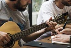 Mann-Spiel-Gitarre schreiben Lied-Musik-Wiederholung stockfotos
