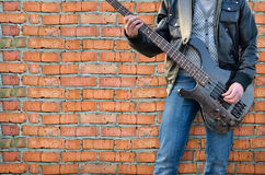 Mann spielt E-Gitarre auf der Hintergrundbacksteinmauer Lizenzfreies Stockfoto