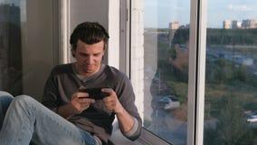Mann spielt ein Spiel im Handy, der im Balkon bei Sonnenuntergang sitzt stock footage
