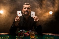Mann spielt Poker mit einer Zigarre und einem Whisky, Karten einer Mannshow zwei in der Hand und auf dem Tisch gewinnt alle Chips stockfotografie