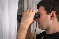 Mann spioniert seine Nachbarn mit Ferngläsern aus lizenzfreie stockfotos