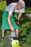 Mann sprüht Anlagen im Garten Stockfotos