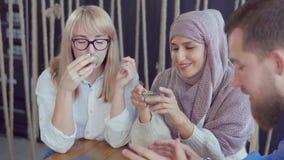 Mann spricht mit zwei arabisch und lustigen Geschichten der kaukasischen Frauen im Café stock video
