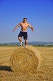 Mann springen unten von den Ballen Stroh Stockfoto