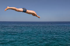 Mann springt in das Meer an einem sonnigen Tag Lizenzfreie Stockfotos