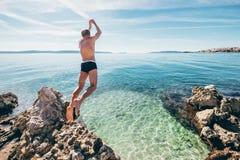 Mann springt in klares Kristallwasser auf adriatisches Seebucht Lizenzfreie Stockfotos