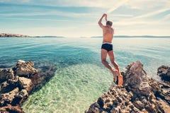 Mann springt in klares Kristallwasser auf adriatisches Seebucht Lizenzfreie Stockbilder