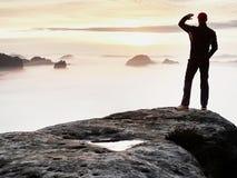 Mann steht allein auf der Spitze des Felsens Wanderer, der zum Herbst Sun am Horizont aufpasst lizenzfreie stockfotografie