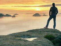 Mann steht allein auf der Spitze des Felsens Wanderer, der zum Herbst Sun am Horizont aufpasst stockfoto