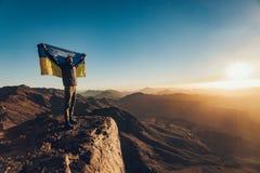 Mann steht auf Berg Sinai und hält Flagge von Ukraine in seinen Händen bei Sonnenaufgang Stockfotografie