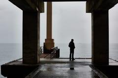 Mann steht auf einem Pier von Meer im schlechten Wetter allein Nebelige Luft stockfoto
