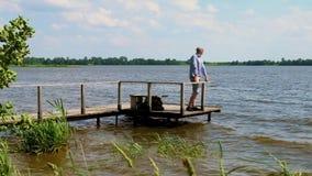 Mann steht auf Pier am See im windigen Wetter stock video