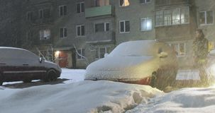 Mann steht nahe bei einem Auto, das durch Schnee getragen worden ist stock video