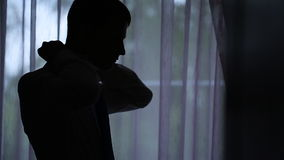 Mann steht nahe Fenster- und Bindungsbindung in dunkel-beleuchtetem Raum stock video