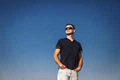 Mann steht stolz und untersucht den Abstand über blauem Himmel Lizenzfreies Stockfoto