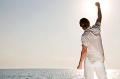 Mann am steigenden Strand die Hand lizenzfreies stockfoto